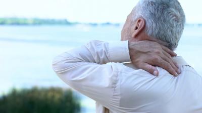 senior man massaging aching neck