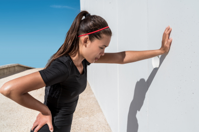 woman leaning on wall experiencing muscle back pain